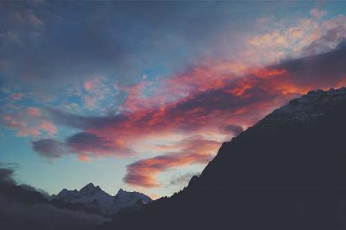 sky snow capped mountain under red clouds and blue sky dusk
