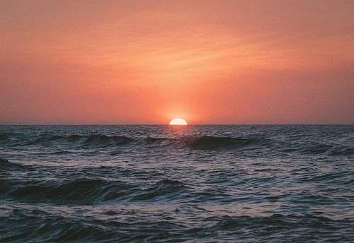 sunrise sunset on body of water sea