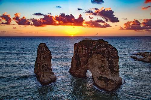 sky two rock formations in body of water beirut