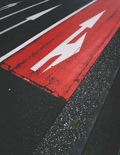 asphalt red and white road during daytime road