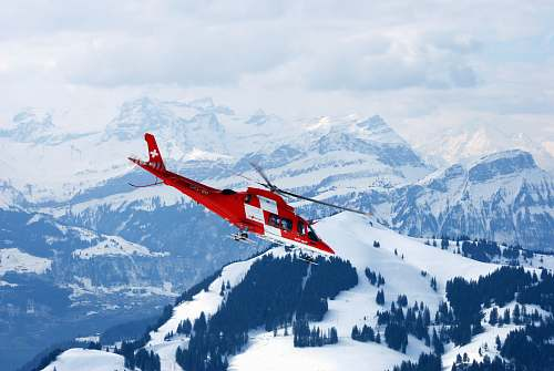snow photo of flight of red and white rescue helicopter during snow daytime glacier