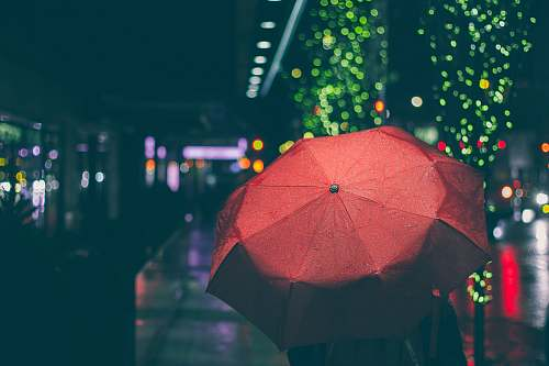 canopy person with red umbrella walking on street during nighttime rain