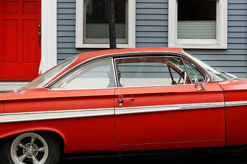 car classic red coupe parks beside gray and white wooden house automobile