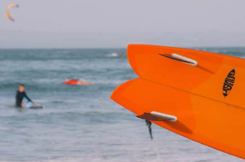person close-up photo of orange surfboard human