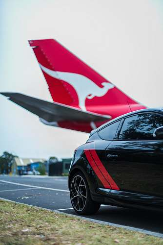 transportation red and white airplane behind a black hatchback automobile