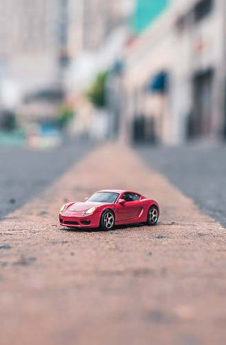 car selective focus photography of red coupe scale model on road toluca