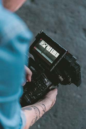 cinematography person holding black DSLR camera video camera