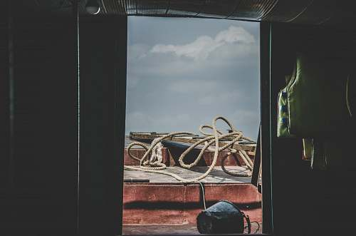 window brown rope on brown wood slab outside building during daytime red