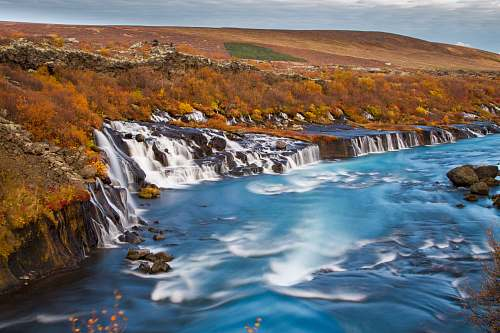 iceland landscape photography of waterfalls surround by brown fiels river