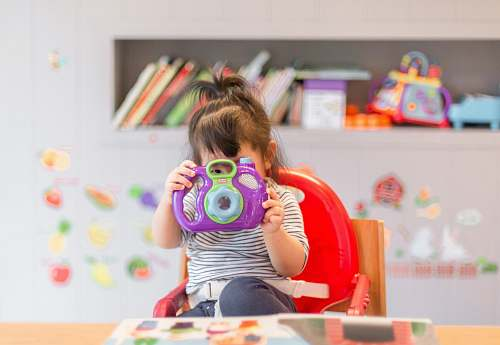 people girl holding purple and green camera toy human
