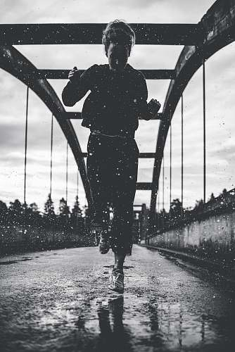 people greyscale photography of woman running on bridge person