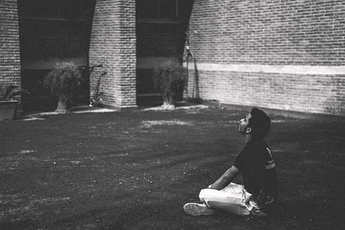 grey man in black t-shirt sitting on grass brick