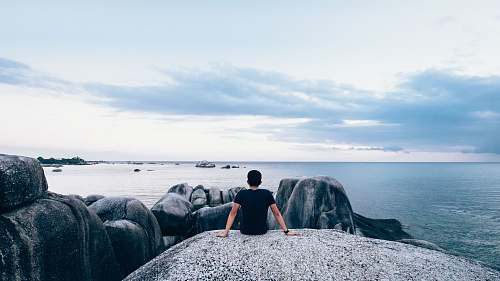 people man sitting on rock beside body of water sea