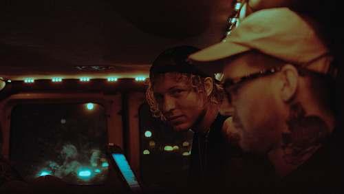 people man wearing cap beside man at nighttime person