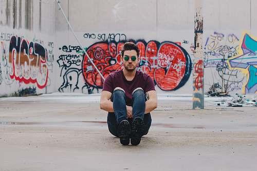 people man wearing purple shirt sitting in front of graffiti wall graffiti