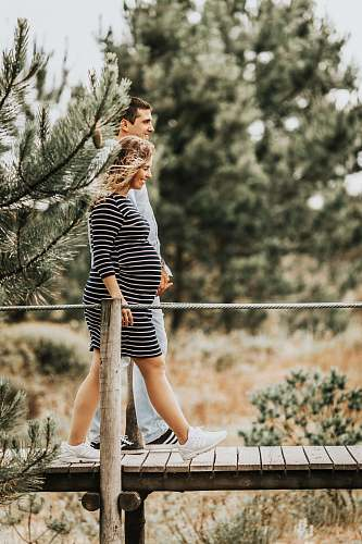 people selective focus photography of couple walking on wooden bridge person