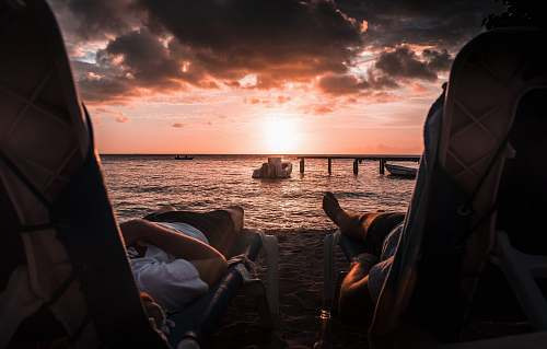 people two person lying on chaise lounge under sunset person