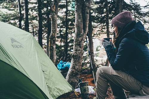 people woman sitting and holding cup of coffee camping