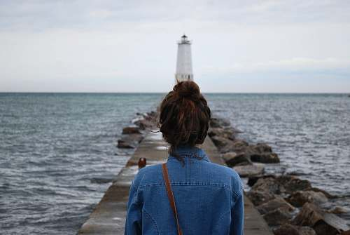 sea woman standing infront of lighthouse near beach water