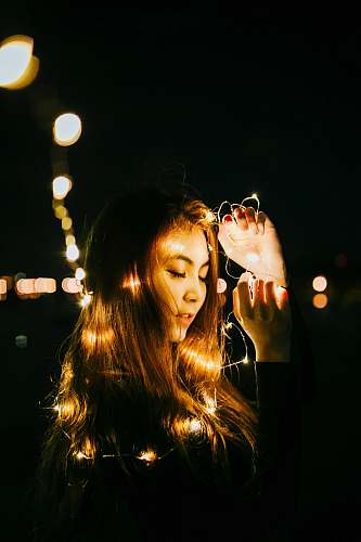 person bokeh photography of woman holding string lights human