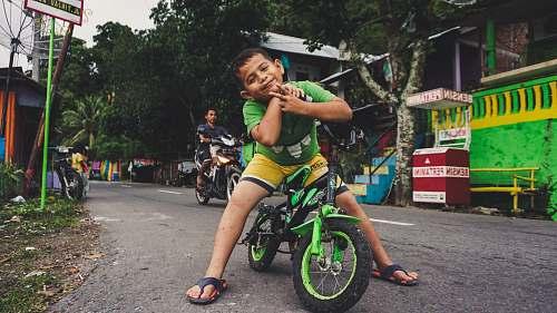 bike boy riding black and green bike near man riding motorcycle at daytime vehicle