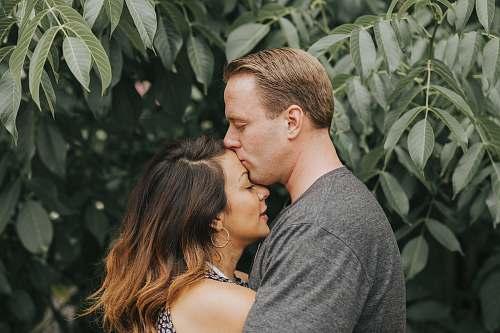 kiss couple hugging near tree leafs kissing