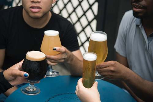 human four person holding glass goblets beer