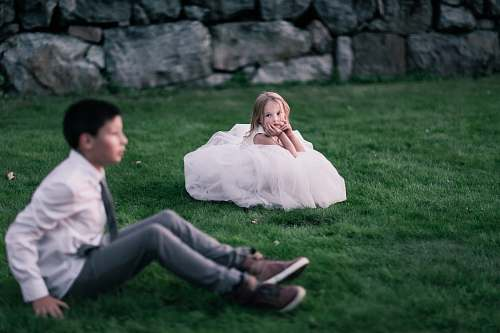 person girl sitting on green grass looking at the boy sitting on green grass human