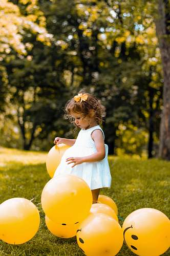 person girl wearing white sleeveless dress beside balloons human