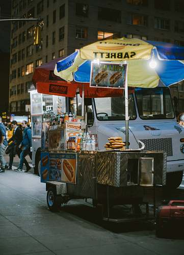 person gray food stall with umbrella near vehicle human