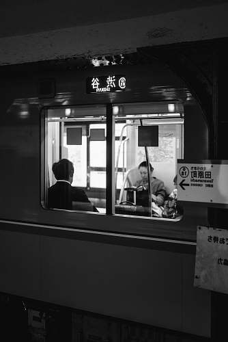 human grayscale photo of two people sitting in train black-and-white