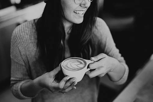 person grayscale photo of woman holding coffee black-and-white