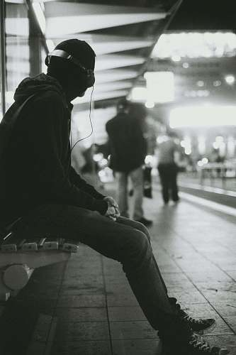 human grayscale photography of a man sitting on bench while listening music person