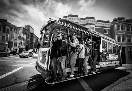 person grayscale photography of group of person riding on vehicle black-and-white
