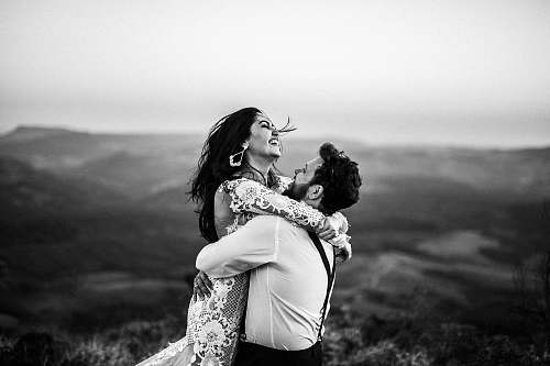 human grayscale photography of man and woman hugging near hill black-and-white