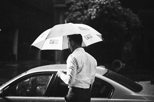 human grayscale photography of man holding umbrella in front of sedan black-and-white