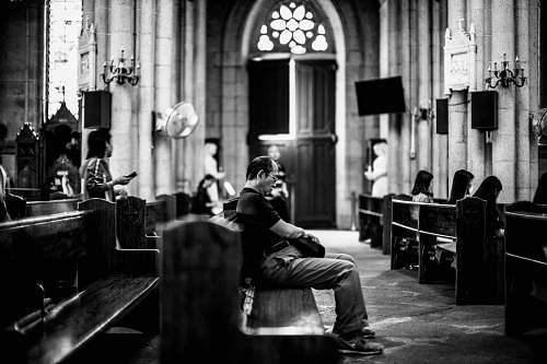 human grayscale photography of man sitting on pew black-and-white