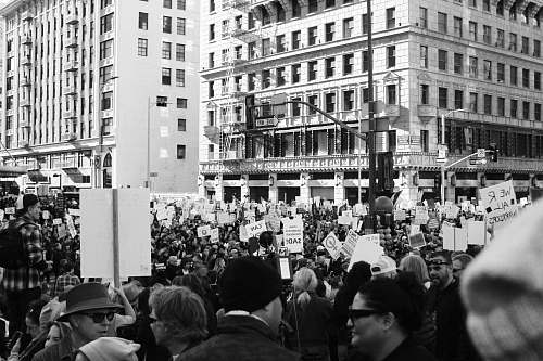 black-and-white grayscale photography of people protesting in front of concrete building crowd