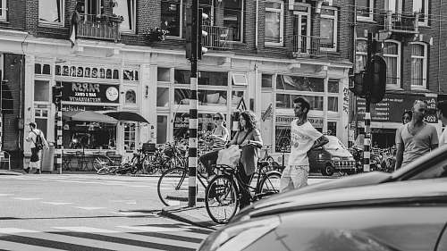 black-and-white grayscale photography of people walking across street bicycle