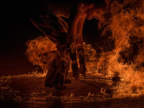 person male fire dancer holding two torches surrounded by fire human