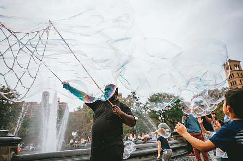 human man and boy performing bubble artworks near fountain at daytime bubble