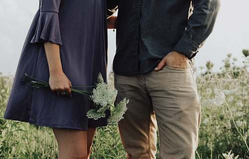 human man and woman standing on white flower field at daytime person