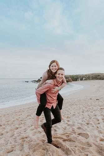 human man carrying woman beside seashore person