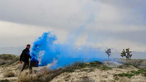 person man holding black box with blue smoke walking on grass field during daytime human