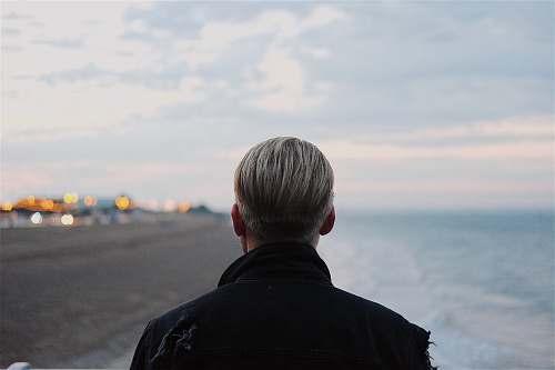 human man in black coat walking on seashore person