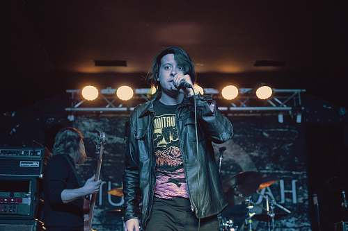 person man in black leather jacket singing with microphone human