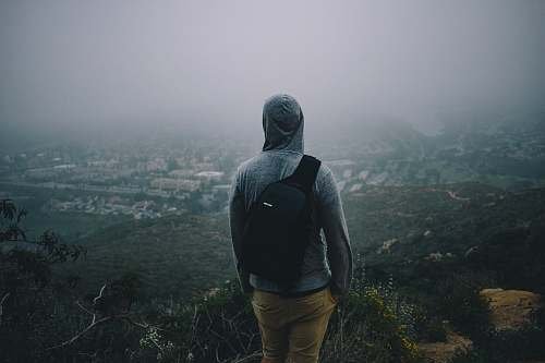 human man in gray hoodie with black backpack looking at the city from mountain peek person