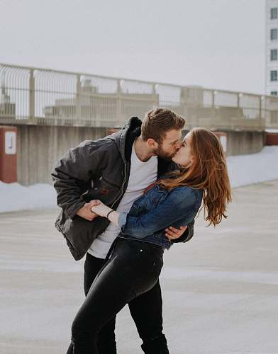 human man kissing woman during daytime person