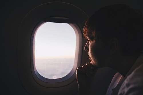 person man looking at window inside plane window