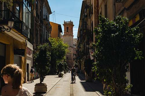 flora man riding bicycle near narrow street surrounded by buildings during daytime jar